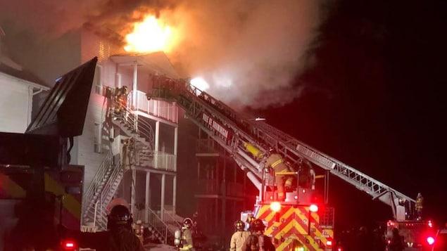 Des pompiers et des camions-échelle à proximité d'un bâtiment en flammes.