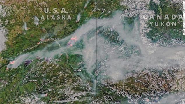 Une image satellite de la frontière entre l'Alaska et le Canada montre de la fumée et des zones de feux de forêt.