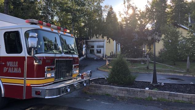 Une résidence détruite par les flammes et un camion de pompier à l'avant.