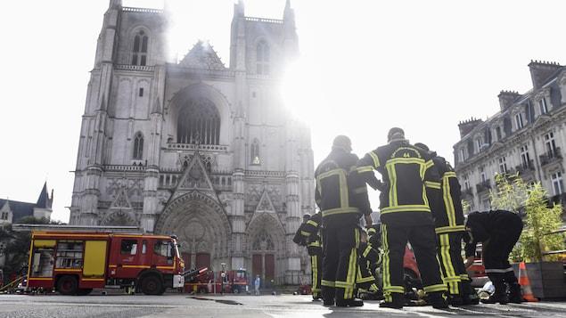 Des pompiers devant la cathédrale Saint-Pierre-et-Saint-Paul de Nantes endommagée par le feu.
