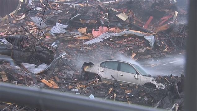 Des voitures incendies au centre des décombres d'un immeuble dévasté par un incendie à Magog.