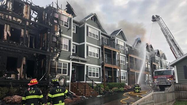 Des pompiers devant une aile calcinée de l'immeuble.