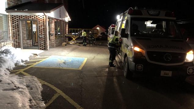 Une ambulance et un ambulancier transportant un patient sur une civière.