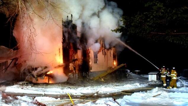 Des pompiers arrosent une résidence en flamme.