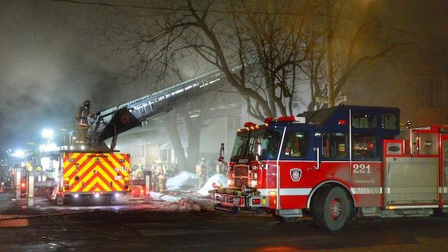 Les pompiers sont à l'oeuvre dans une épaisse fumée.