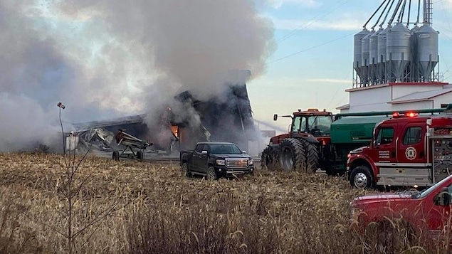 Des pompiers sont présents aux abords d'un garage agricole en flamme.