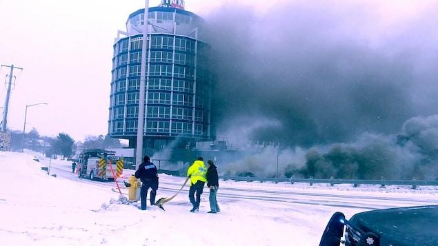 Un édifice d'où s'échappe une fumée épaisse et noire. Un camion de pompier est stationné devant.