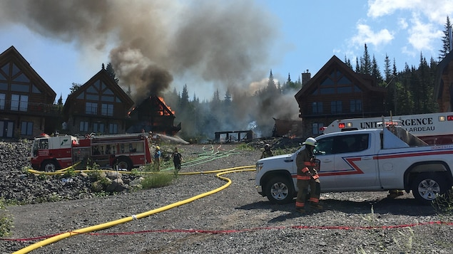 Des camions de pompiers devant les chalets ravagés par les flammes.