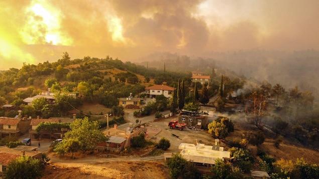 Photo aérienne montrant des maisons entourées par un incendie sur la côte sud de la Turquie, près de la ville de Manavgat.