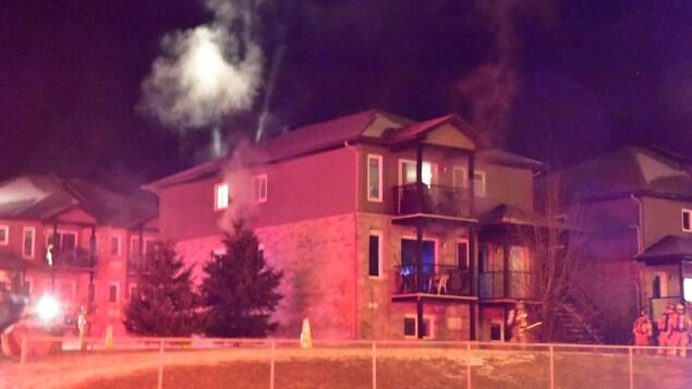 De la fumée sort d'un immeuble à plusieurs endroits.