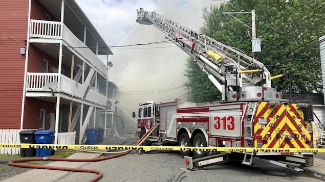 Camion de pompier qui arrose des bâtiments.