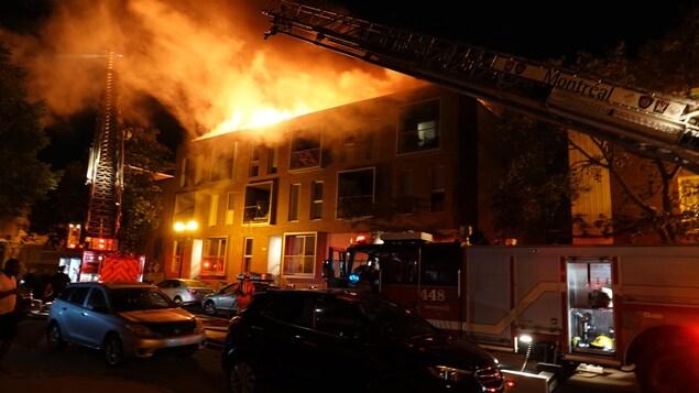 Des flammes surgissent du toit d'un immeuble de trois étages.