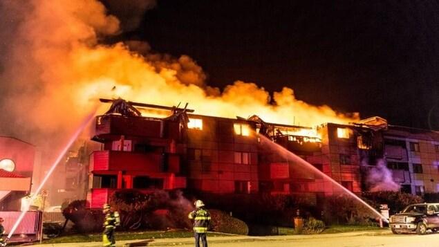 Des pompiers utilisent leurs lances à eau sur un immeuble en flammes.