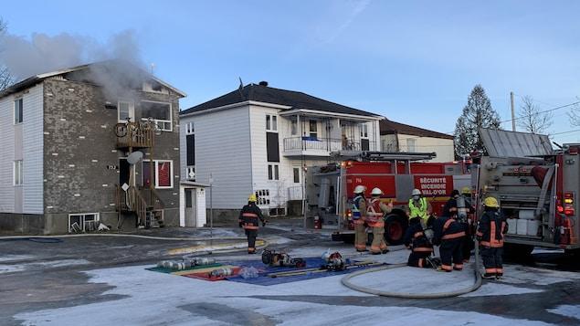 De la fumée s'échappe du bâtiment. Huit pompiers sont près de leur camion dans la rue.
