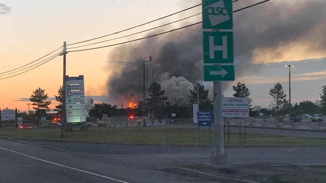 Les flammes sortent de la bâtisse abritant une clinique médicale. La fumée monte très haut dans le ciel.