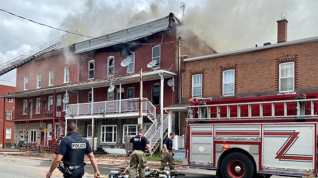 Des pompiers et des policiers interviennent devant un édifice d'où s'échappe de la fumée.