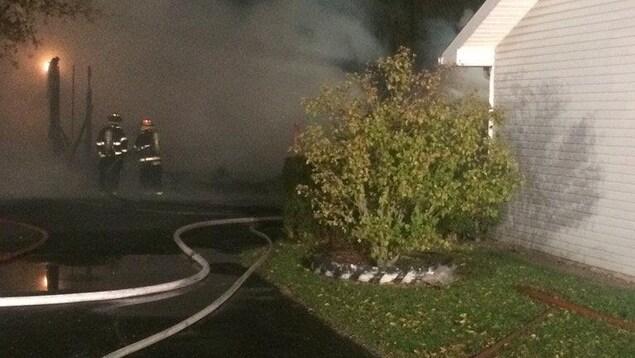 Des pompiers combattent un incendie. Une importante fumée sort d'un batiment blanc