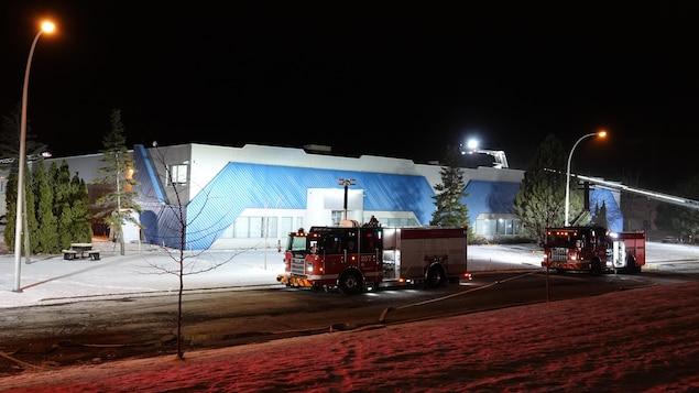 Des camions de pompier sont devant un bâtiment.