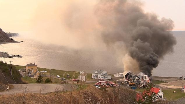 Une colonne de fumée s'élève d'un bâtiment tombé en ruines. Des sapeurs arrosent le brasier.