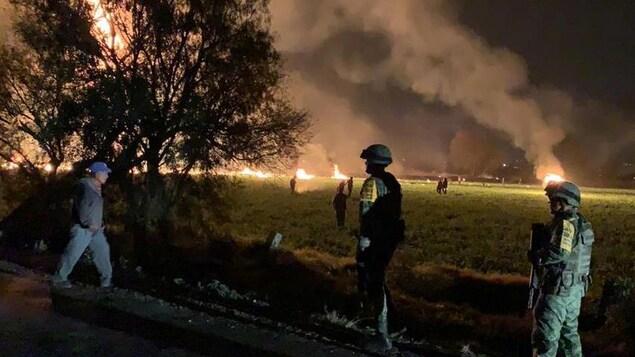 Dans la municipalité de Tlahuelilpan (Hidalgo), des militaires observent les flammes qui engloutissent une zone après l'explosion d'un oléoduc.