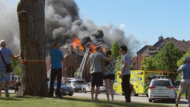 Une poignée de personnes regardent des flammes s'échapper d'un immeuble à logements.