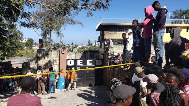 Des gens se sont rassemblés devant les portes de l'orphelinat incendié.