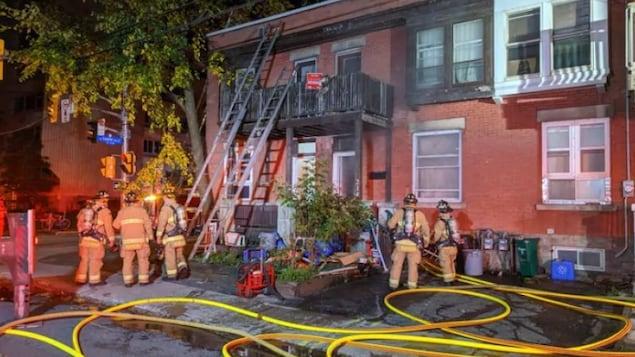 Cinq pompiers et des grandes échelles devant une maison en rangée.