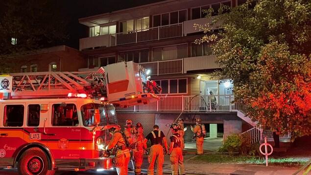 Des pompiers et un camion de pompiers devant un édifice résidentiel