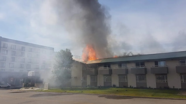 Des flammes et de la fumée jaillissent du motel de deux étages.