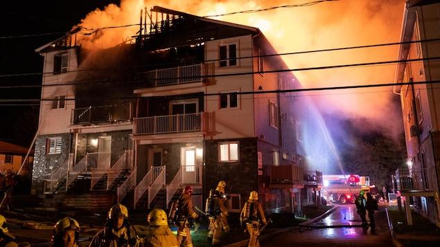 Des pompiers devant un immeuble dont on voit des flammes sortir du toit.