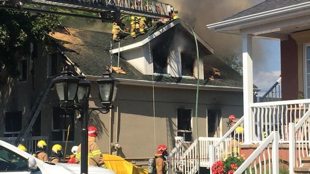 Une maison avec plusieurs pompiers autour. On voit de la fumée sortir par les fenêtre et la toiture.