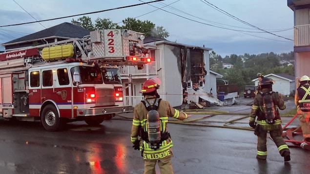 Des pompiers interviennent pour éteindre un duplex en feu.