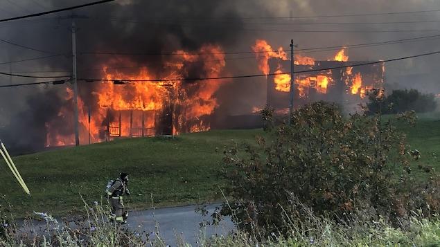 Deux maisons sont en proie aux flammes pendant qu'un pompier travaille sur le terrain.
