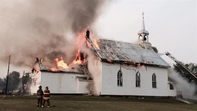 Des flammes s'échappe du toit de l'église