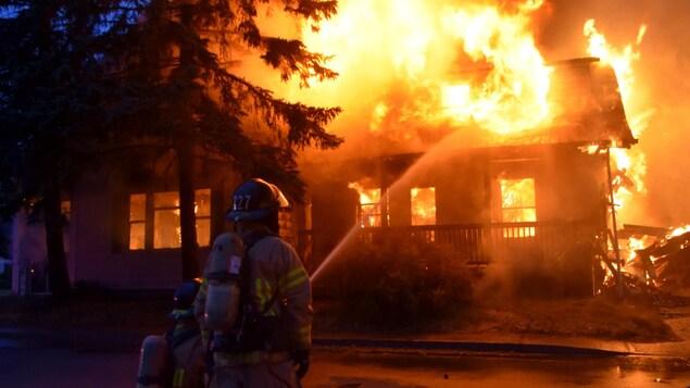 Deux pompiers arrosent une résidence en flamme.