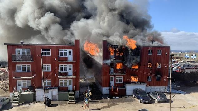 Une épaisse fumée noire sort d'un immeuble de logements en flammes.
