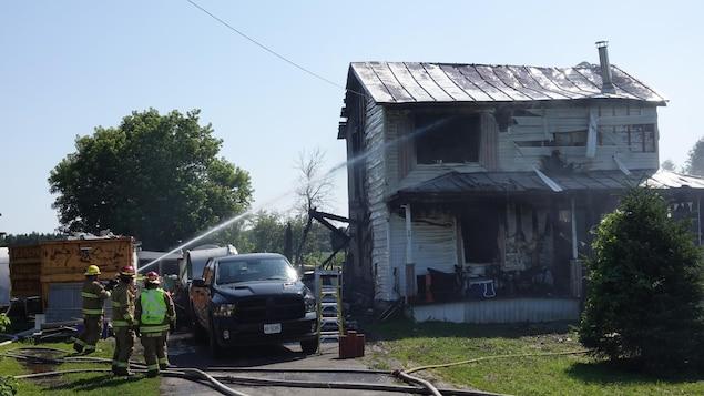 Trois pompiers arrosent le deuxième étage de la maison.