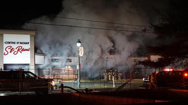 De la fumée enveloppe le centre commercial.
