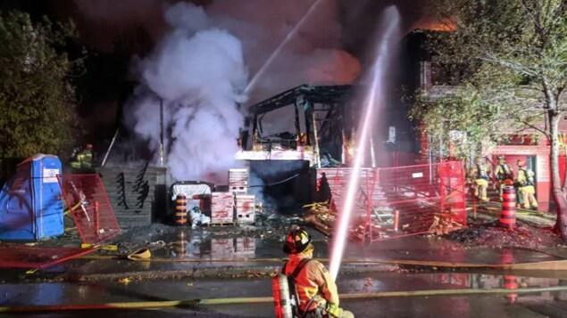 Un pompier dirige sa lance vers un incendie.