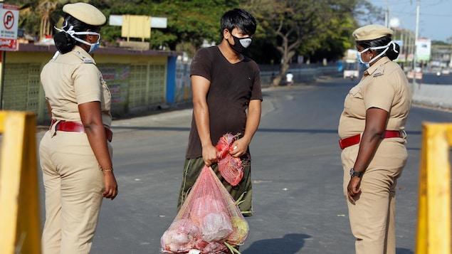 Un homme portant un masque et deux policières