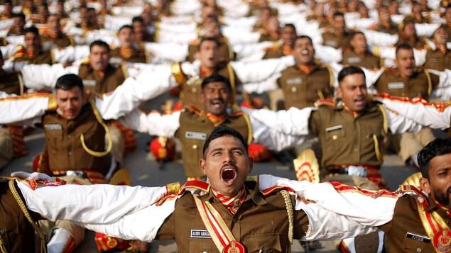 Des soldats indiens se tenant par les épaules rient lors d'une séance de yoga.
