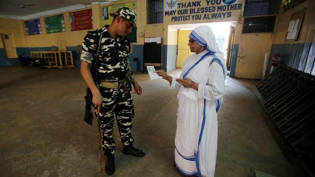 Un soldat vérifie les papiers d'identité d'une religieuse.
