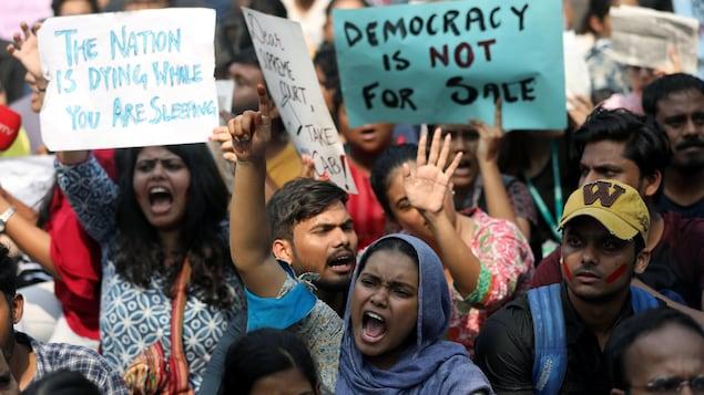 Hommes et femmes manifestent en criant des slogans à Delhi.