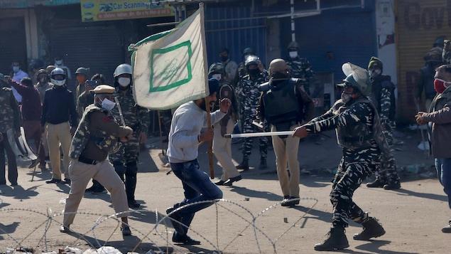 Des policiers matraquent un manifestant.
