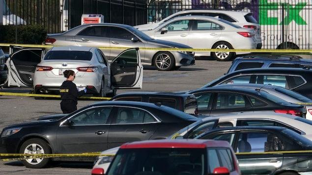 Entre les voitures immobiles dans un stationnement, des cordons de sécurité sont tendus. Une technicienne de la police se déplace entre les véhicules.