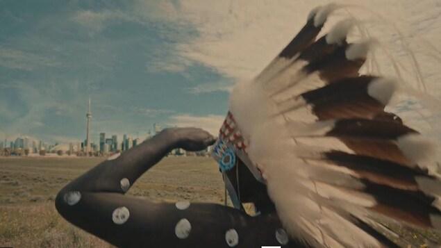 Une personne vêtue d'une coiffe amérindienne regarde au loin vers la ville de Toronto.