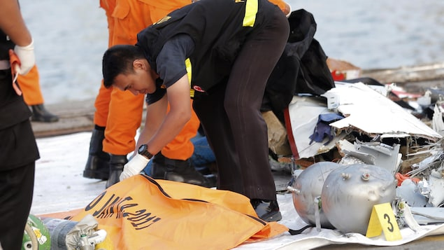 Un homme examine le contenu d'un sac mortuaire.