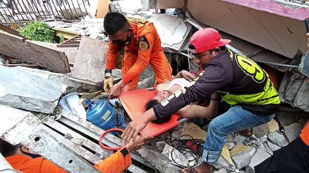Des sauveteurs évacuent un homme blessé.