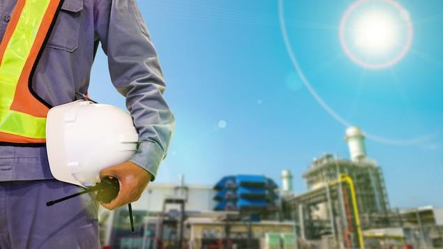 Un travailleur tient un casque et un walkie-talkie sur un chantier.