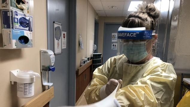 Une infirmière enfile des gants de protection.